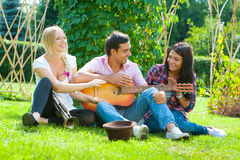 Young friends play the guitar and trumpet Royalty Free Stock Images