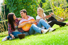 Young friends play the guitar and trumpet Royalty Free Stock Photo