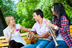 Young friends play the guitar and trumpet Stock Photography