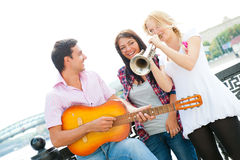 Young Friends Play The Guitar And Trumpet Royalty Free Stock Photography