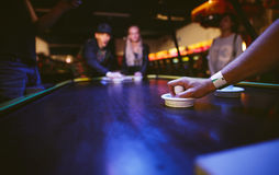 Young friends playing air hockey game Royalty Free Stock Photo