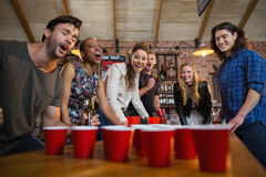 Young friends playing beer pong game in bar. Young friends playing beer pong game on table in bar Royalty Free Stock Image