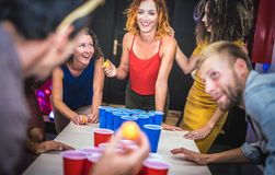 Young friends playing beer pong at youth hostel - Free time travel concept with backpackers having unplugged fun at guesthouse. Happy people on playful royalty free stock image