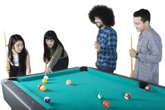 Young friends playing billiard together Royalty Free Stock Image