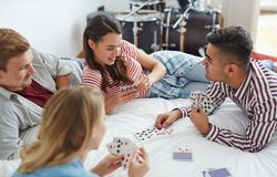 Leisure game. Young friends playing cards while relaxing on bed at leisure Royalty Free Stock Images