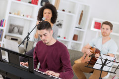 Young friends playing guitar piano and signing Royalty Free Stock Images