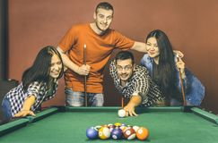 Young friends playing pool at billiard table saloon - Happy friendship. Concept with fashion people having fun together and sharing time at snooker gameroom stock image