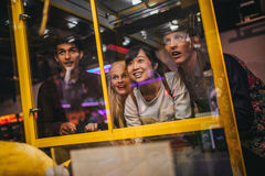 Young friends playing toy grabbing game. Cheerful young friends playing toy grabbing game at amusement park. Happy women selecting a random soft toy in a vending Stock Images