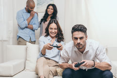 Young friends playing video games at home Stock Photos