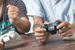 Young friends playing video games in their apartment. Stock Image