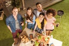 Young friends preparing food and smiling at camera at picnic Royalty Free Stock Image
