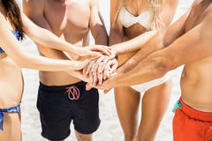 Young friends putting their hands together on the beach Royalty Free Stock Photos