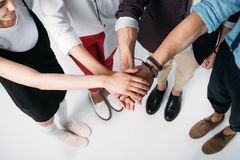 Young friends putting their hands together stock photography