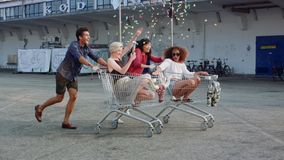 Young friends racing grocery carts. Multiracial group of young people enjoying outdoors with shopping trolley race stock video