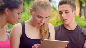 Young friends reading bad news on tablet. Closeup of young people shocked stock video