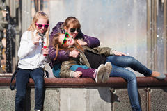 Young friends relaxing against a city fountain Stock Photography