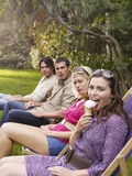 Young Friends In Row On Deckchairs At Garden Stock Photo