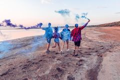 Young friends running with hand flare or fusee royalty free stock image