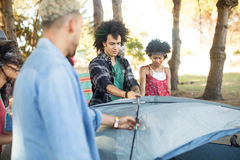 Young friends setting up tent Royalty Free Stock Photography
