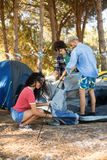 Young friends setting up tent on field Royalty Free Stock Photography