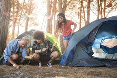 Young friends setting up tent at forest Stock Photo