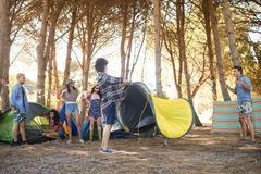 Young friends setting up their tents at countryside stock images