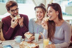 Friends sharing pizza in a indoor cafe. Young friends sharing pizza in a indoor cafe royalty free stock photography