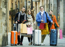 Young friends in shopping tour. Portrait of positive young friends chasing streets in shopping tour Stock Photos