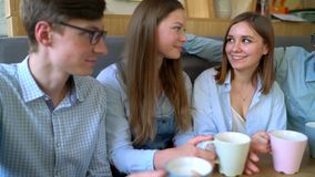 Young friends sit in a cafe, drink coffee and have fun communicating. Slow motion. Happy smiling friends sit in a cafe, drink coffee and have fun communicating stock video