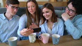 Young friends sit in a cafe, drink coffee and have fun communicating. Slow motion. Happy smiling friends sit in a cafe, drink coffee and have fun communicating stock footage