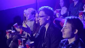 Young friends sit in a cinema with popcorn and drinks and watch a comedy film. stock video