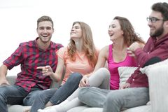 Young friends sitting on the couch and rooting for their favorite team Royalty Free Stock Photography