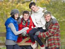 Young friends sitting on fence Stock Photos