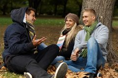 Young friends sitting on ground in autumn park royalty free stock image
