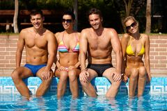 Young friends sitting by pool smiling. Attractive young people sitting by outdoor pool, smiling, looking at camera Royalty Free Stock Photos