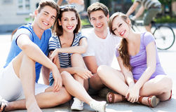 Young friends sitting on street Royalty Free Stock Image