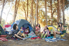 Young friends sitting together at campsite royalty free stock photo