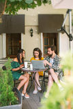 Young friends with smartphones and laptop in cafe with coffee Royalty Free Stock Photography