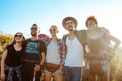 Young friends smiling, rejoicing, looking into distance, standing in field. Royalty Free Stock Photo