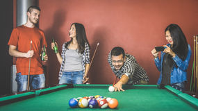Young friends talking and playing pool at billiard table saloon. Happy friendship concept with fashion people having fun together and drinking beer stock images