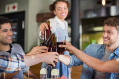 Young friends toasting beer bottles in pub. Cheerful young friends toasting beer bottles in pub Royalty Free Stock Image
