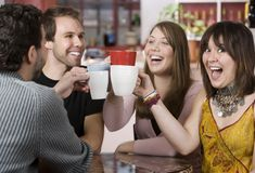 Young Friends Toasting with Coffee Cups Stock Photo