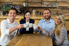 Young friends toasting with coffee cups royalty free stock images