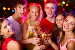 Young friends touching the glasses with each other. Happy group of young friends touching the glases with each other royalty free stock photos