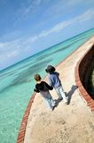Young friends on tropical stroll. Two boys walking on a pier in tropical waters Stock Image