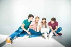 Young friends using laptop Stock Photos