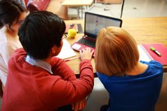 Young friends using laptop together Stock Images