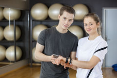 Young Friends Using Mobile Phone And Smart Watch In Gym Stock Image