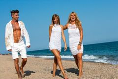 Young friends walking along sunny beach. Royalty Free Stock Photos