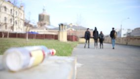 Young friends walking on the streets - bottle of alcohol drink left empty on the stand. Mid shot stock video footage
